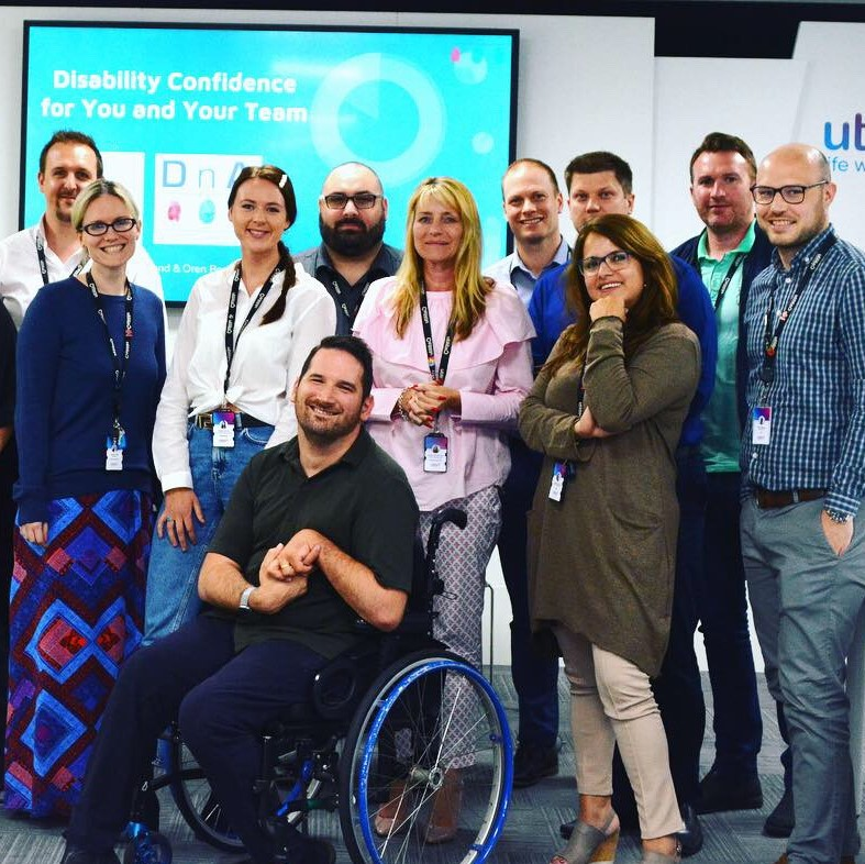 A group of people standing or sitting in front of a presentation board that reads: Disability confidence for you and your team. Everyone is looking at the camera and smiling.