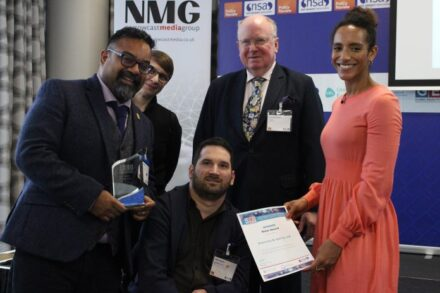 Atif, a brown man wearing glasses and standing holding the Noon Award trophy, and Adam, a white man sitting in his wheelchair, are smiling at the camera. To their left is Afua Hirsch, a Black woman, Dr Jana Javornik, a white-appearing person, and David Robinson, a white-appearing man.