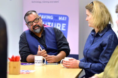 Members of the D&A team around a table in the office. In focus is Atif, a brown man wearing glasses, a black shirt and blue waistcoat. He is speaking and looking intently at Giedre, a white woman with blonde straight hair, who is sat to his right.