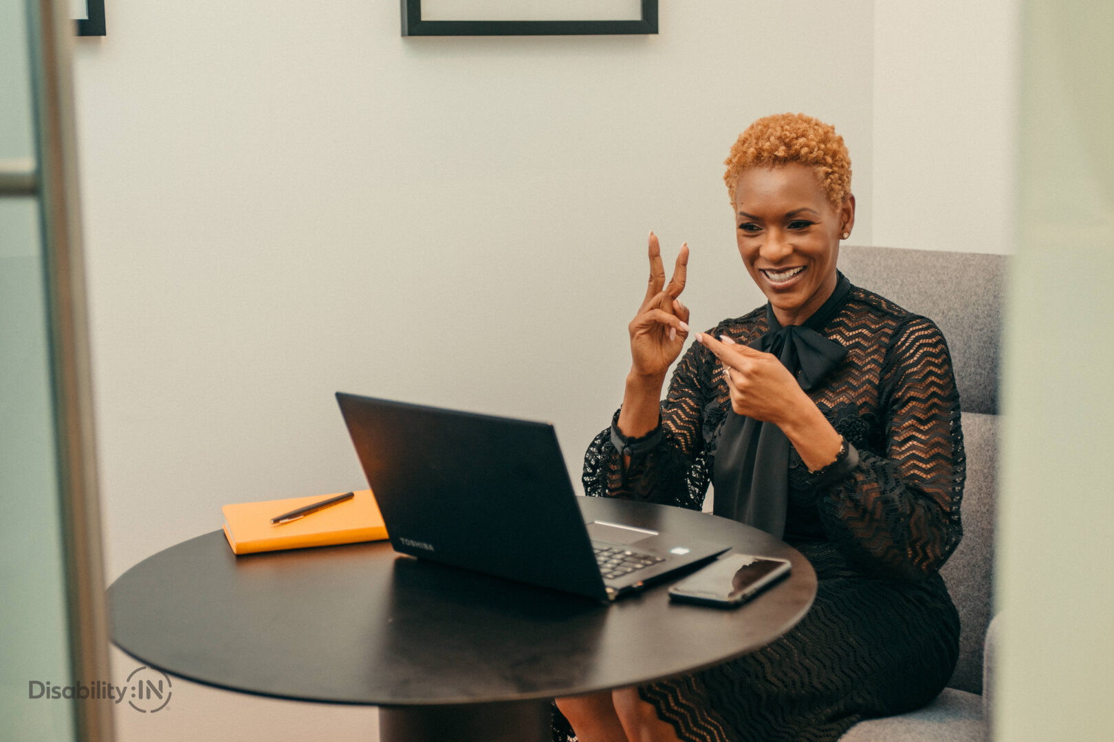 A woman of colour smiles and signs in American Sign Language to a laptop as if it's a video meeting.