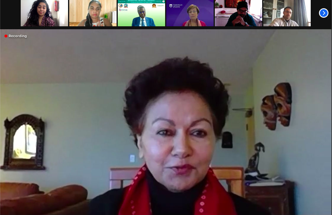 Screenshot of a Zoom call in speaker view. The speaker is Professor Asha Kanwar, a woman with short dark hair, wearing a bright red scarf. Her facial expression is positive and suggests she is mid-speech.