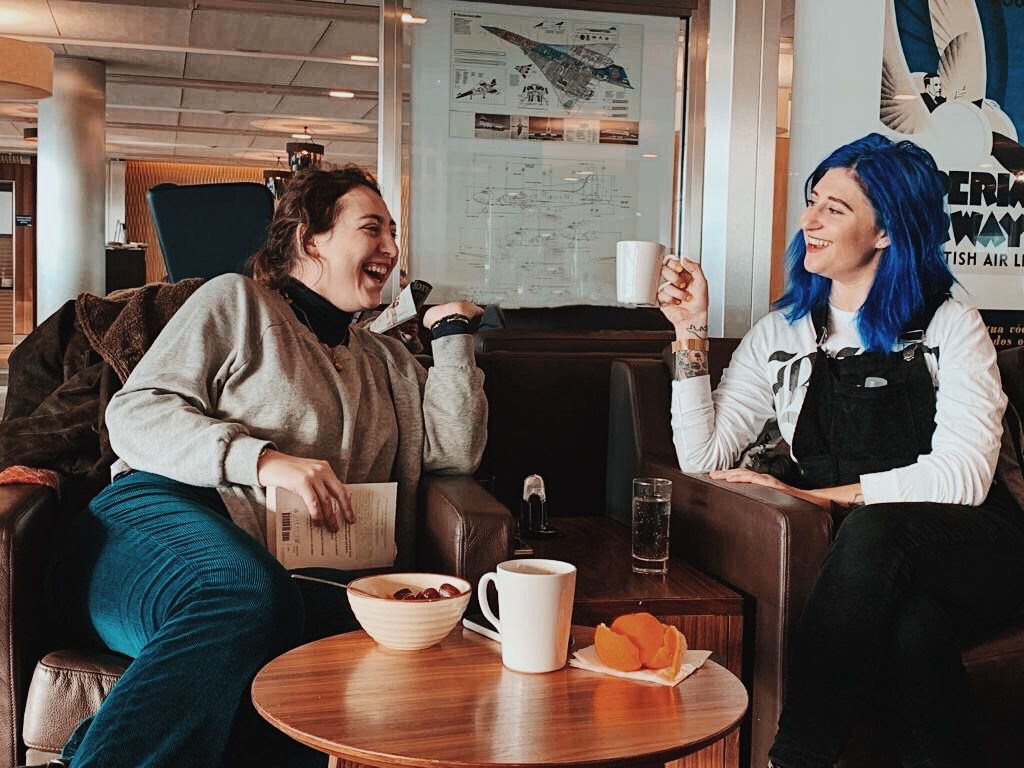 Nikita, a white, Jewish woman with curly brown hair is sitting with a closed book in her hand and laughing while facing her sister Tash. Tash is a white, Jewish woman with blue hair and tattoos on her arm. She is sitting with a mug in her hand, smiling and looking at her sister. Between them is a small table with a mug, cereal bowl and orange peels on it.