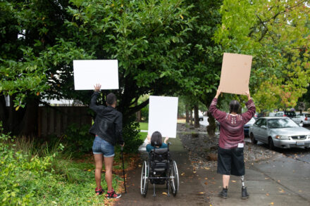 Three disabled people of color (a Black non-binary person with a cane, a South Asian person in a wheelchair, and an Indigenous Two-Spirit person with a prosthetic leg) block a neighborhood street while holding up cardboard signs. The photo is shot from behind everyone.