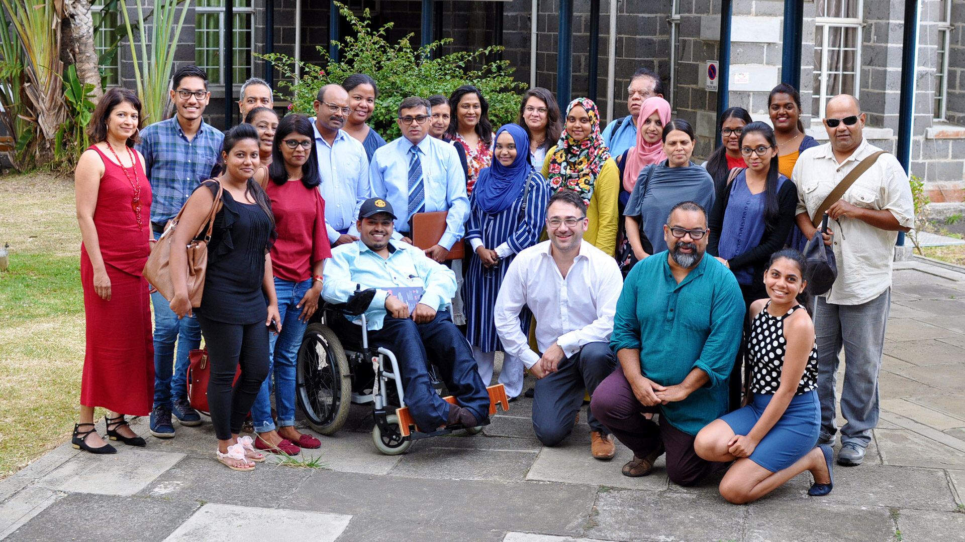 A group of people standing, sitting in wheelchairs or kneeling while smiling at the camera. They are a mixture of different races, skin colours, genders, ages and disabilities. They are in a bright, outdoor setting in front of a modern bricked building.Amongst them is Atif, CEO of Diversity and Ability, a brown man with short dark hair and glasses.