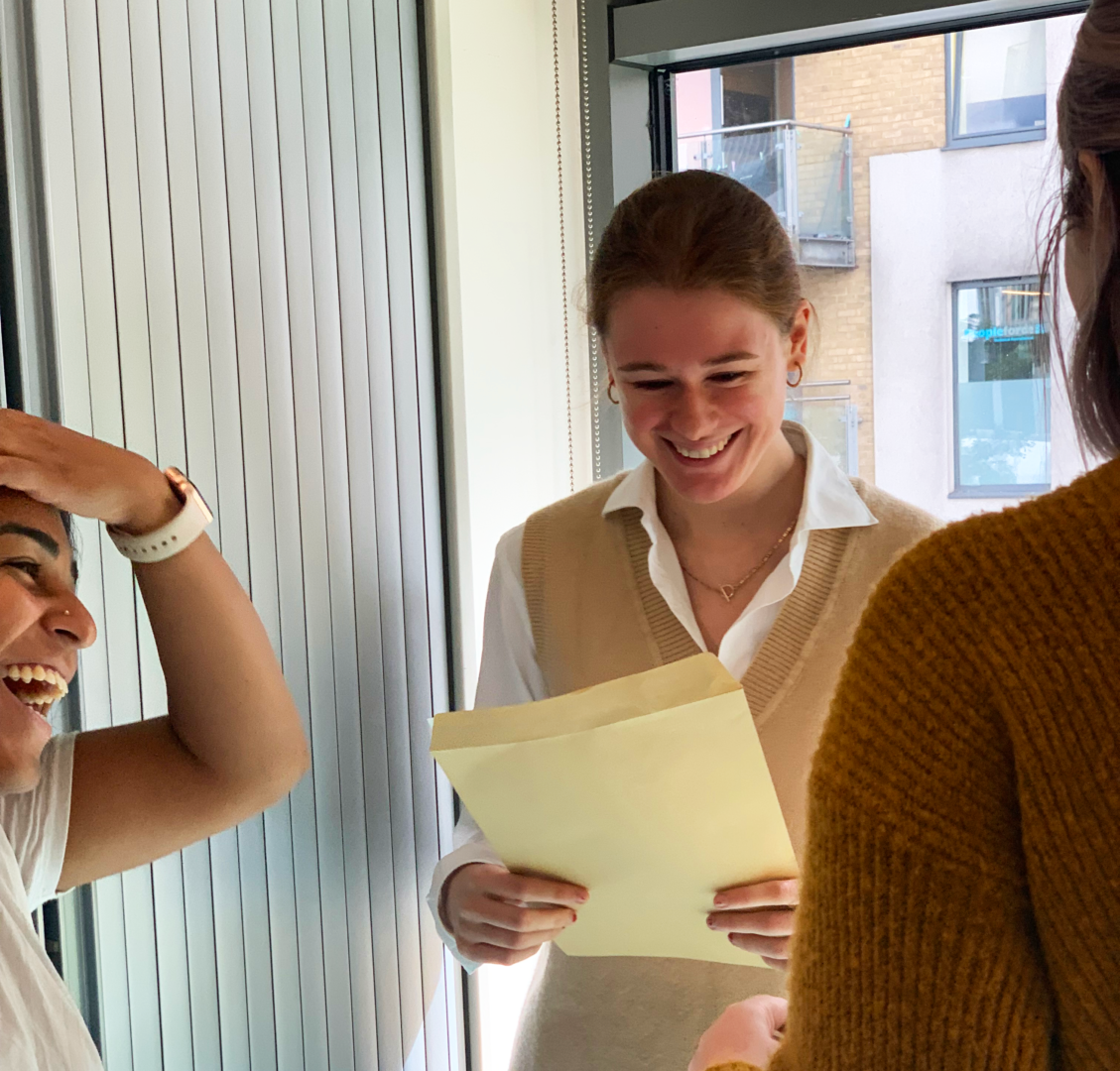 Three women standing in a circle smiling. In focus is Emily, a white woman wearing a white shirt, who is staring at an envelope and smiling. To the right is Ruksar, a brown woman, who is pushing hair out of her face and smiling.