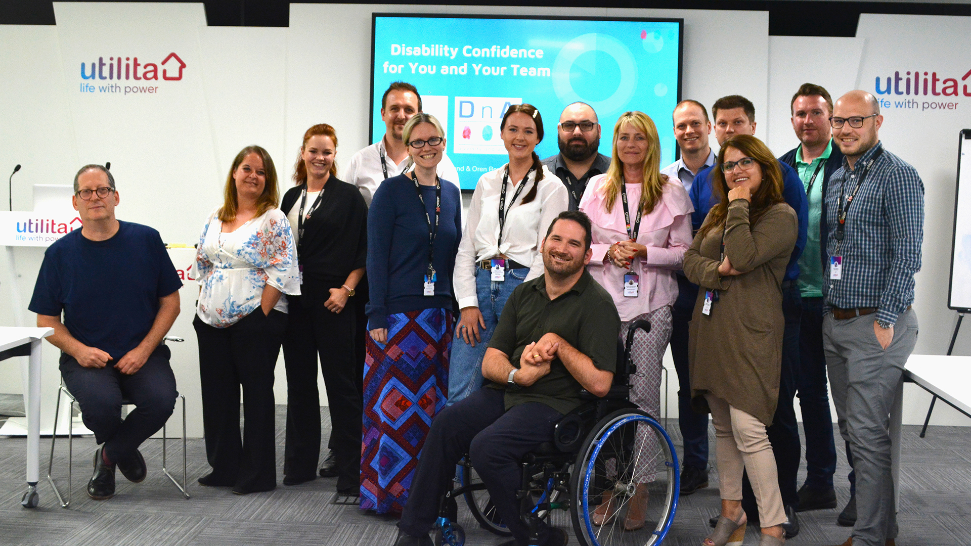 A photo of the Utilita team with D&A's Adam Hyland (Director of Accessibility and Inclusion) and Oren Ben-Dor (Assistive Technology Trainer). All are smiling. In the background is the powerpoint which displays the title of the workshop the team is about deliver: Disability Confidence for You and Your Team